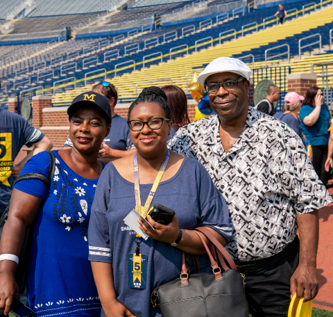 Three people smiling at the Michigan Football Stadium