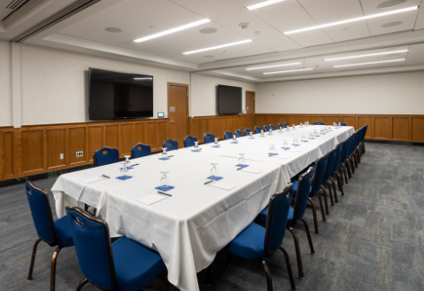 Large meeting room with long table, seating for 30 and audiovisual equipment.