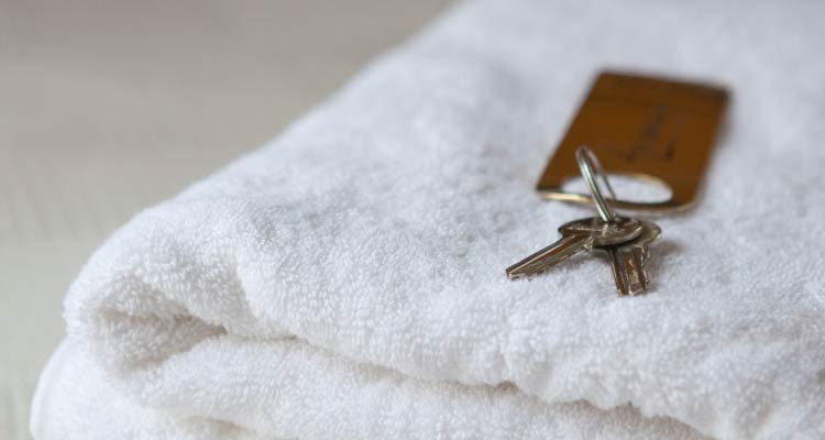 A set of keys on top of a hotel towel.