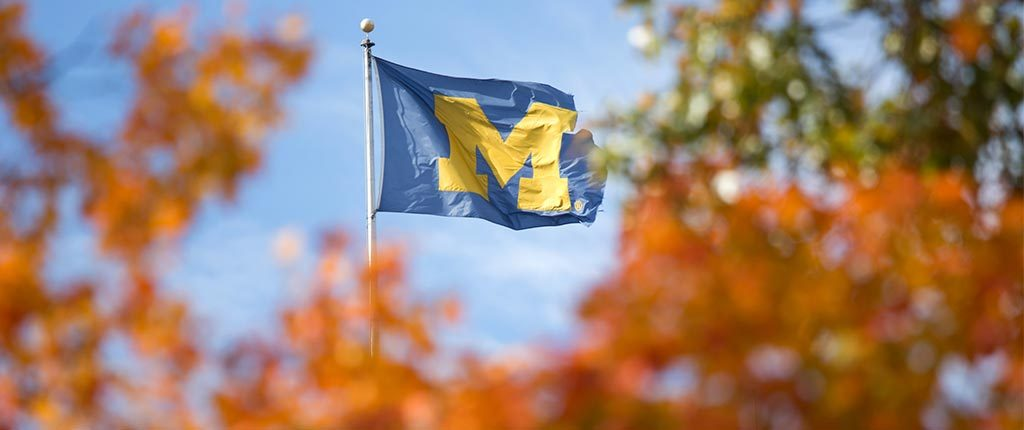 The block M flag is spotted beyond some fiery-colored trees in autumn.