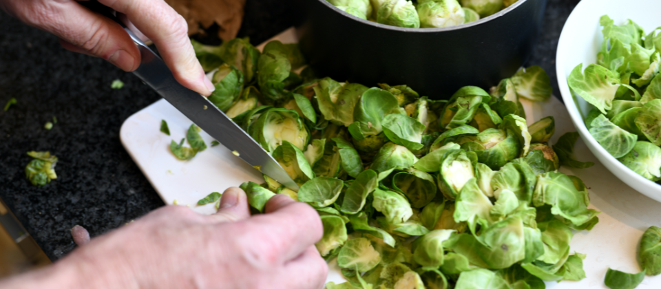 Chef using knife to chop Brussels sprouts.