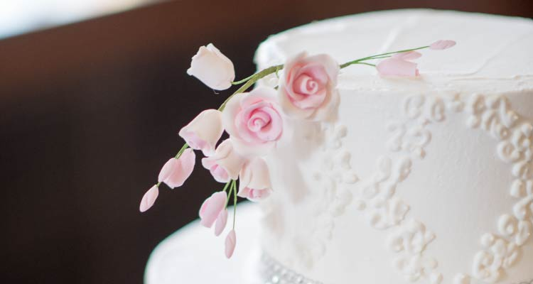 A white tiered cake with pink flowers.